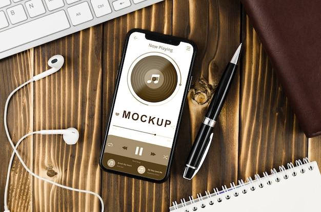 Plat lag smartphone mock-up met oortelefoons en pen