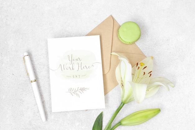 Plat leggen uitnodigingskaart met ambachtelijke envelop, lily en macarons