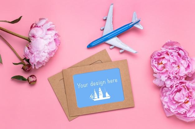 Plat leggen van blanco ambachtelijke papieren kaarten met roze pioenrozen en vliegtuig op roze.