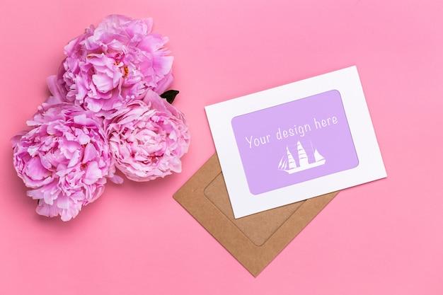 Plat leggen van blanco papier kaarten met drie pioen hoofden op een roze