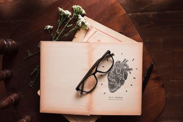 Plat leggen van boeken met glazen en bloemen