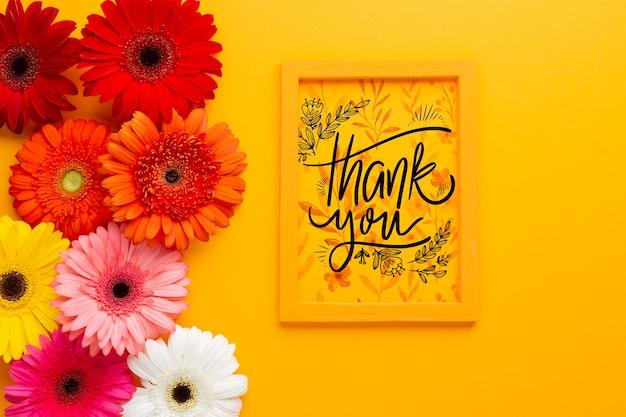 Plat leggen van frame en bloemen op gele achtergrond