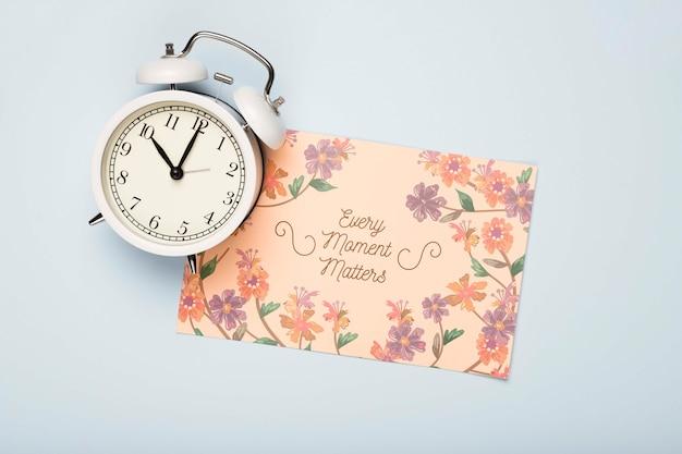 Plat leggen van klok en bloemen kaart voor de lente