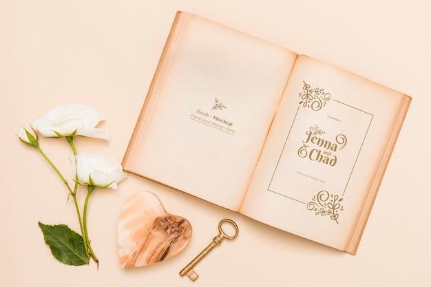 Plat leggen van open boek met rozen en sleutel