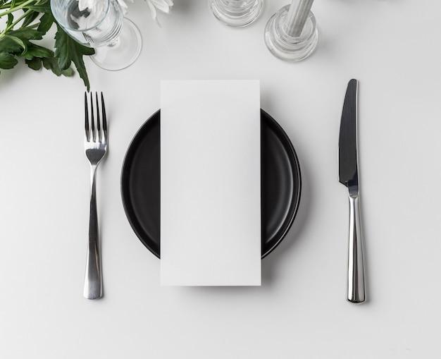 Plat leggen van tafelopstelling met mock-up van het lentemenu en bestek