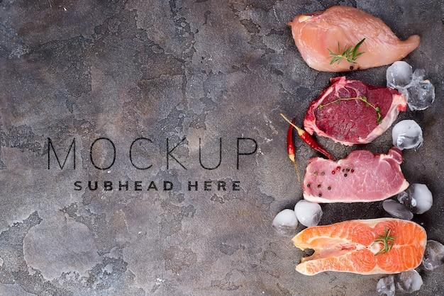 Pollo crudo, carne y pescado con hielo y especias maqueta en piedra.