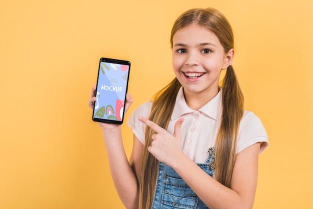 Portret dat van een jong meisje mobiele telefoon houdt