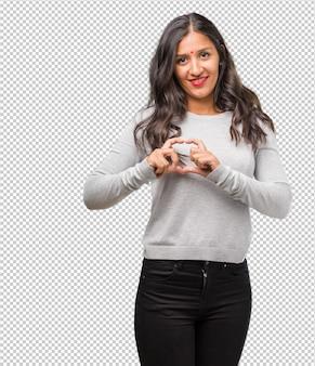 Portret die van jonge indische vrouw een hart met handen maken, die het concept liefde en vriendschap uitdrukken, en gelukkig glimlachen