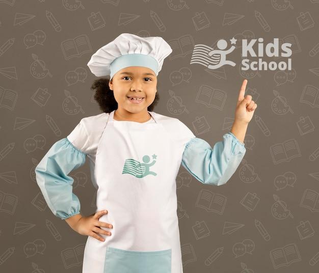 Portret van een jong meisje die zich voordeed als chef-kok