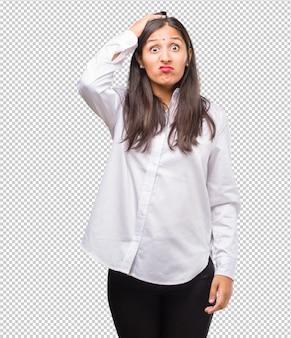 Portret van een jonge indiase vrouw bezorgd en overweldigd, vergeetachtig, realiseert zich iets.