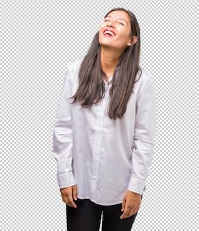 Portret van een jonge indiase vrouw die lacht en plezier heeft, ontspannen en vrolijk is, voelt zich zelfverzekerd en succesvol