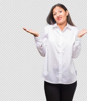 Portret van een jonge indiase vrouw die twijfelt en haar schouders ophaalt, concept van besluiteloosheid en onzekerheid, onzeker over iets