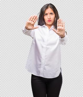 Portret van een jonge indiase vrouw serieus en vastberaden, hand in hand, stop gebaar, ontkennen concept
