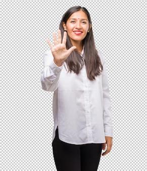 Portret van een jonge indische vrouw die nummer vijf, symbool van het tellen, concept wiskunde tonen, zeker en vrolijk