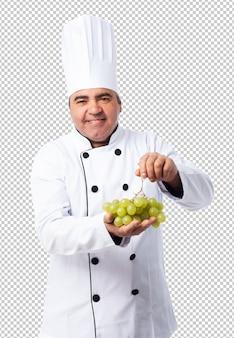 Portret van een kokmens die een druivenbos houden