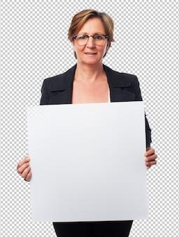 Portret van een rijpe bedrijfsvrouw die een banner houdt