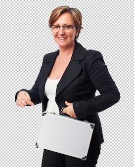 Portret van een rijpe bedrijfsvrouw die een koffer houdt