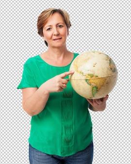 Portret van een rijpe vrouw die een aardebol houdt