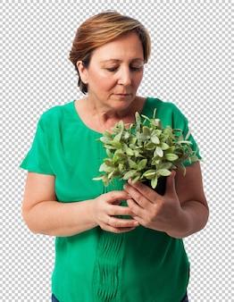 Portret van een rijpe vrouw die een plant behandelt