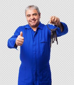 Portret van een slotenmaker die een oude sleutelsbos houdt