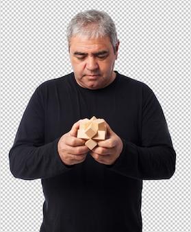Portret van een volwassen man die een puzzel probeert op te lossen