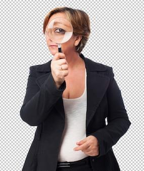Portret van een volwassen zakenvrouw kijkt door een vergrootglas