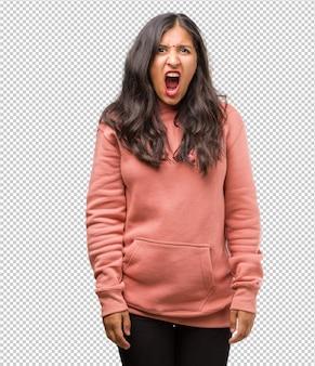 Portret van fitness jonge indiase vrouw boos schreeuwen, uitdrukking van waanzin en mentale instabiliteit, open mond en half geopende ogen, waanzin concept