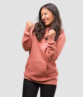 Portret van fitness jonge indiase vrouw erg blij en opgewonden, het verhogen van wapens, het vieren van een overwinning of succes, het winnen van de loterij