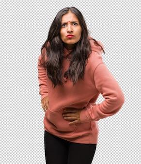 Portret van fitness jonge indiase vrouw erg boos en overstuur, zeer gespannen, woedend, negatief en gek schreeuwen