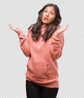 Portret van fitness jonge indiase vrouw gek en wanhopig, onbeheerst schreeuwen, grappige krankzinnige vrijheid en wild uitdrukken