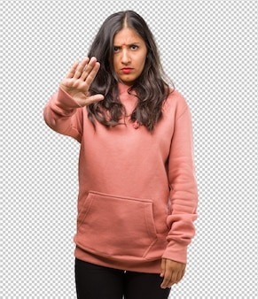 Portret van fitness jonge indiase vrouw serieus en vastberaden, hand in de voorkant, stop gebaar, ontkennen concept
