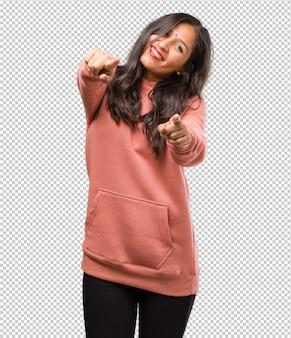 Portret van fitness jonge indiase vrouw vrolijk en glimlachen wijzend naar de voorkant
