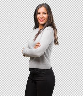 Portret van jonge indiase vrouw kruising zijn armen, glimlachen en gelukkig, zelfverzekerd en vriendelijk