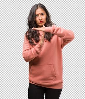 Portret van moe en verveelde geschiktheids jonge indische vrouw, die een time-outgebaar maken, moet wegens het werkstress ophouden, tijdconcept
