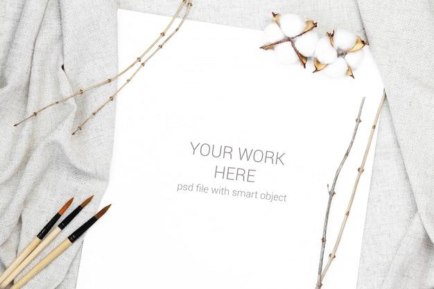 Postal de maqueta con pincel y rama de conífera