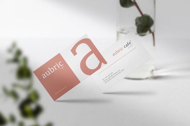 Premium schoon minimaal visitekaartje mockup bovenop wit met bladeren en licht. psd-bestand.