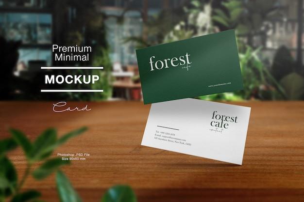 Premium schoon minimaal visitekaartje mockup op houten tafel in bos café en lichte schaduw.