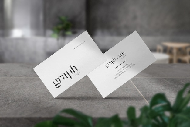 Premium schoon minimaal visitekaartje mockup op steen in grijs café en lichte schaduw.