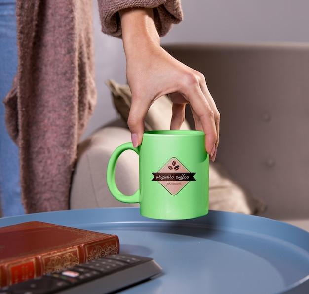 Primer mano que sostiene la taza de café verde