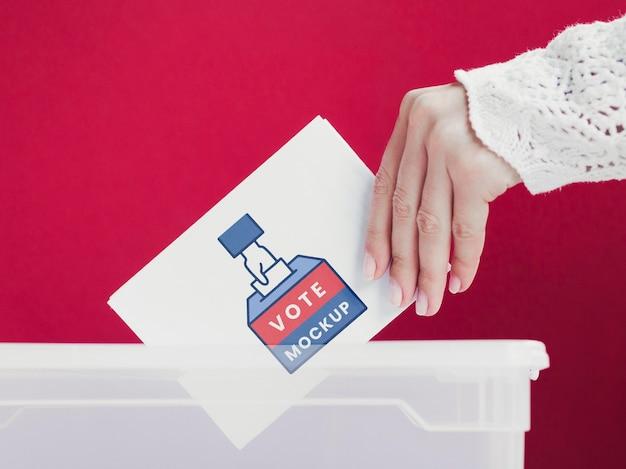 Primer plano femenino poniendo boleta de maqueta en caja