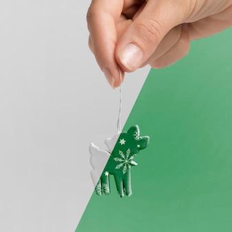 Primer plano mano sujetando decoración de renos