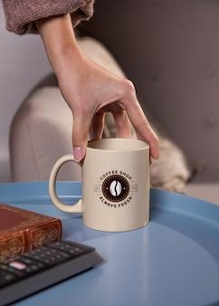 Primer plano mano sujetando la taza de café