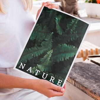 Primer plano de las manos mostrando una revista de naturaleza simulacro