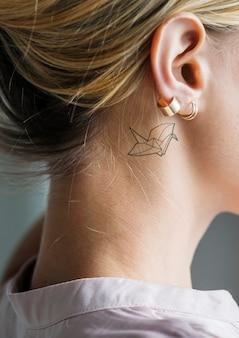 Primer plano de un simple detrás del oído tatuaje de una mujer joven
