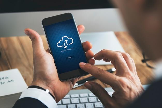 Primo piano di uomo d'affari utilizzando smartphone con simbolo di cloud computing