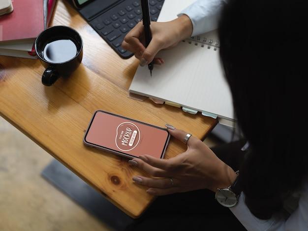 Primo piano sul lavoratore utilizzando il telefono mockup per la ricerca
