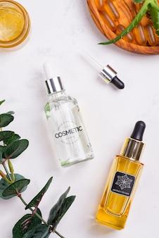 Prodotti naturali di bellezza con crema cosmetica, capsule di gel omega-3 e siero in bottiglie di vetro