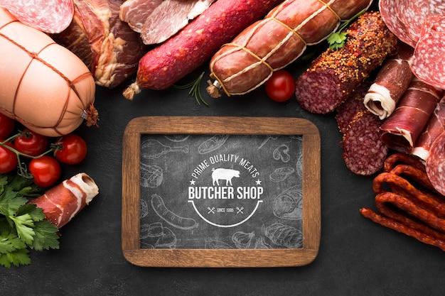 Productos de carne planos con maqueta de pizarra