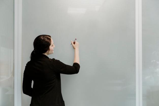 Profesor tomando notas en la pizarra