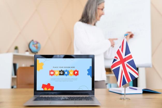 Profesora de inglés de pie junto a una computadora portátil de maqueta